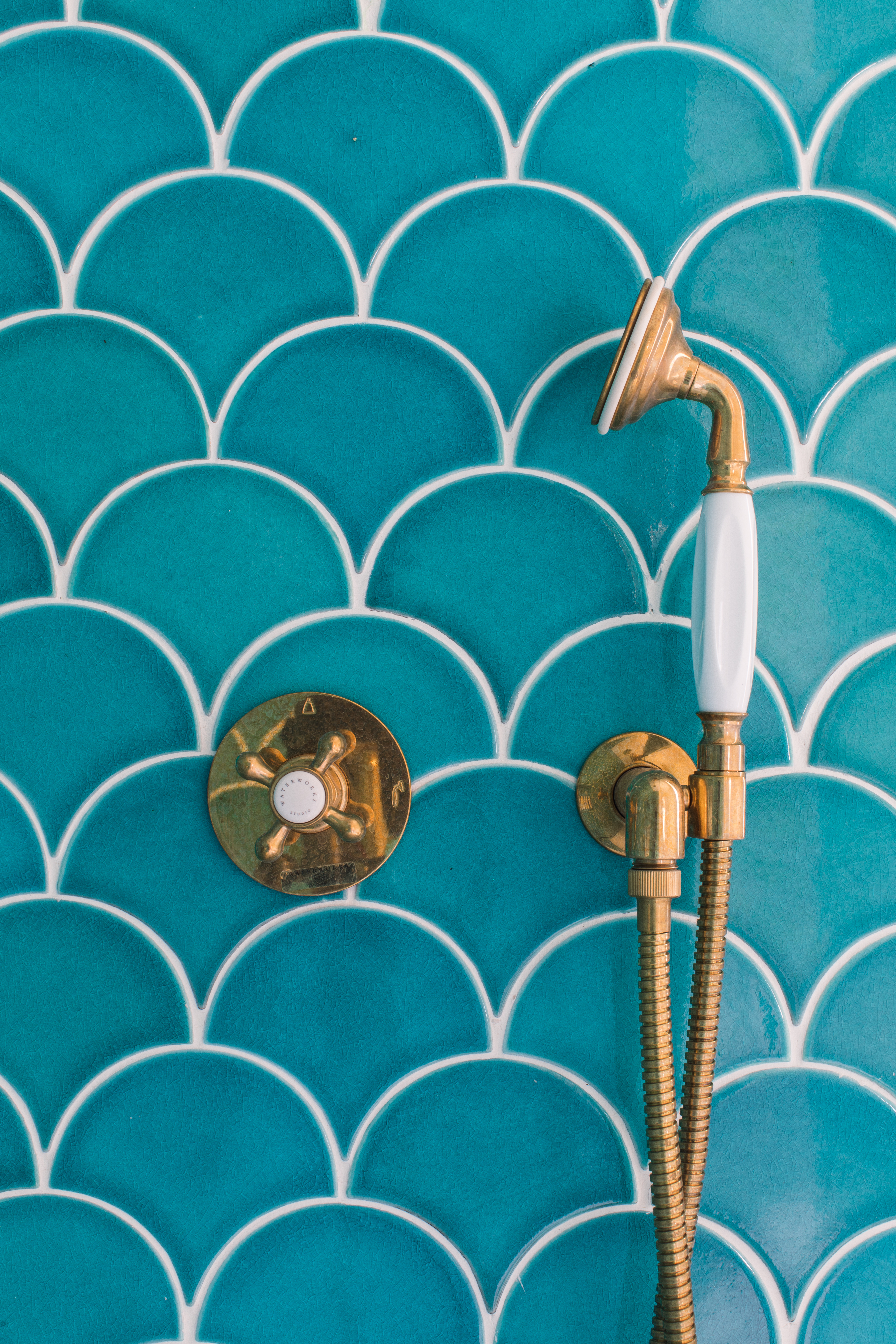 Interior designer Will Taylor, creator of Bright Bazaar, gives his beach house guest bath a getaway-worthy upgrade with white and blue bathroom tiles in an eclectically patterned blend.
