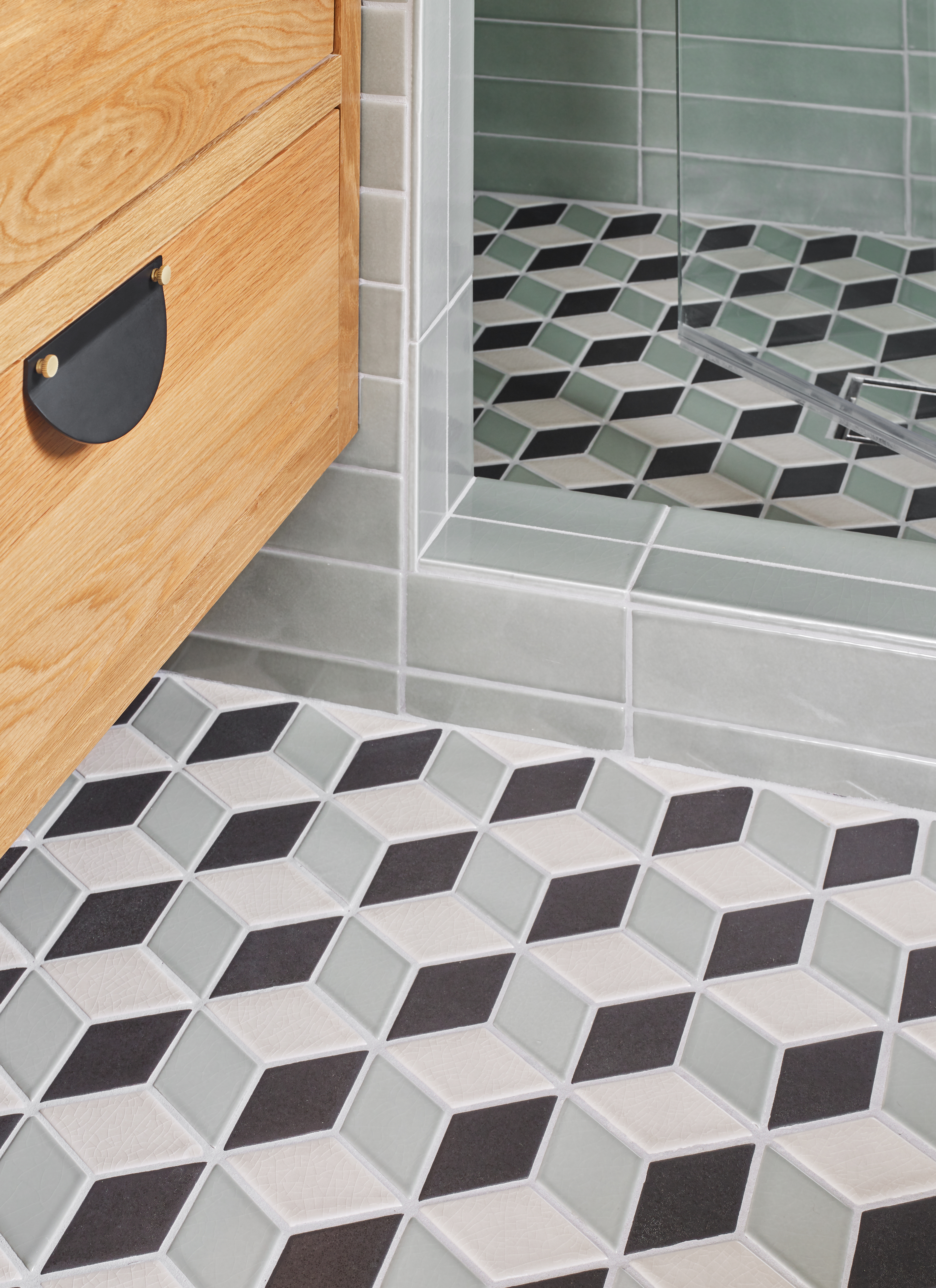 """Playfully called the """"stair step floor"""", interior designer Jessica Davis' patterned bathroom floor tiles maximize the """"wow"""" factor in this petite space. Modern tiles in our Rosemary green tie it all together."""