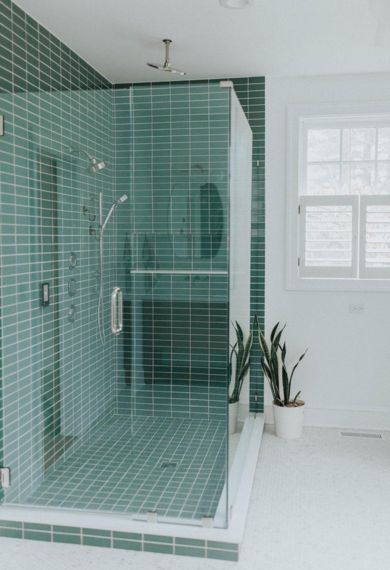 green shower tile and hexagon floor tile bathroom